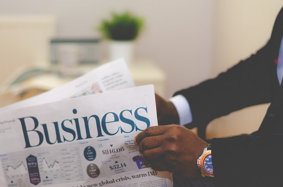 The image shows a man reading the business pages of the daily newspaper depicting business expenses